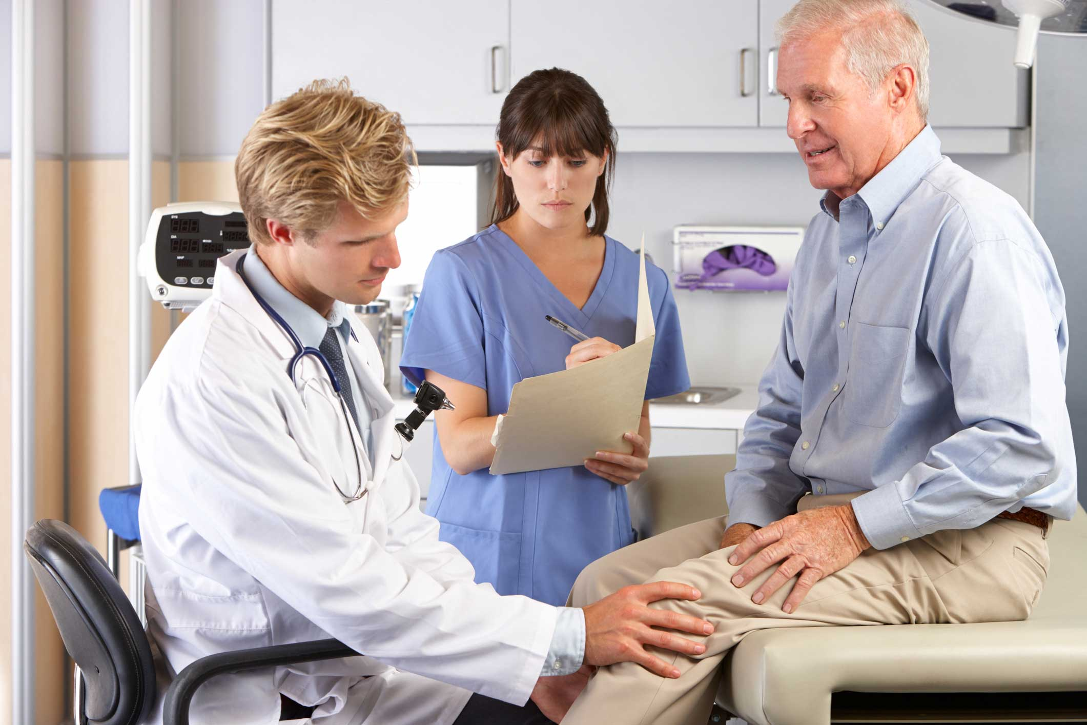 Doctor Examining Patient's Knee with Nurse Writing Down Notes
